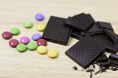 stock photo of bonbon  - Dark chocolate with pile of colored bonbons - JPG