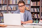 stock photo of concentration man  - Confident young man working on laptop while sitting at the desk and in font of bookshelf - JPG