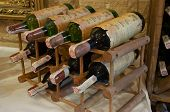 stock photo of wine cellar  - wine bottles laying in wooden rack - JPG