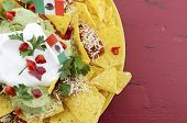 image of nachos  - Happy Cinco de Mayo party table with nachos food platter and bright orange red and pink napkins on a red wood background - JPG