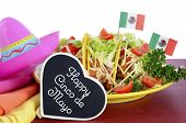 stock photo of tacos  - Happy Cinco de Mayo bright colorful party food with platter of tacos on red wood table - JPG