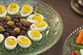 stock photo of kalamata olives  - Deviled eggs kalamata and green olives served with carrots jimaca and cherry tomatoes as a before dinner horderve