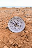 foto of orientation  - Orientation Concept Metal Compass on a Rock in the Desert - JPG