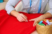 stock photo of tailoring  - Male dressmaker tailor fabric on table - JPG