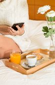 image of wench  - Woman eating breakfast in bed while looking at your mobile phone - JPG