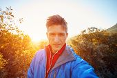 stock photo of blazer  - young  man make selfie on the morning mountains background - JPG
