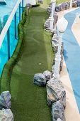 stock photo of miniature golf  - Green felt on miniature golf course on a luxury cruise ship - JPG