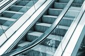 stock photo of escalator  - Shining metal escalator moving up blue toned monochrome photo - JPG