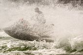 stock photo of ski boat  - A jet ski rider ploughs through spray and wake thrown up by a boat in a channel - JPG