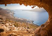 stock photo of cave  - Male rock climber climbing along a roof in a cave. Kalymnos island, Greece.