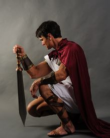 stock photo of sword  - a warrior is crouched down with a sword - JPG