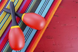 picture of mexican fiesta  - Happy Cinco de Mayo background with red and yellow maracas on Mexican style fabric and distressed red wood table - JPG