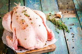 foto of whole-grain  - organic raw whole chicken with thyme peppers and garlic on a rustic table