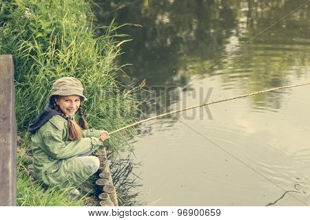 little fisher girl sitting on a river bank with a rod smiling