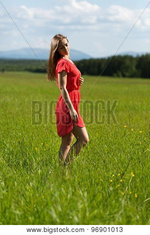 Beautiful Girl In A Red Dress In A Field