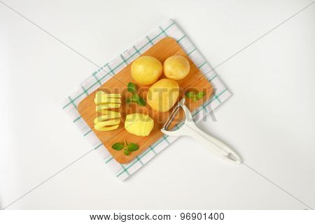 raw potatoes and peeler on wooden cutting board and checkered dishtowel