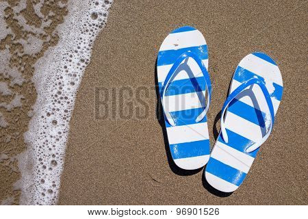 Flip flops on a sandy ocean beach