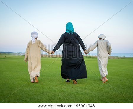 Arabic family on green meadow in nature