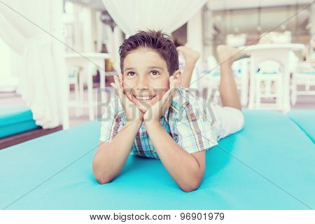Cute kid enjoying on turquoise bed