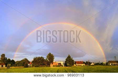 Rainbow At Sunset Over The Village