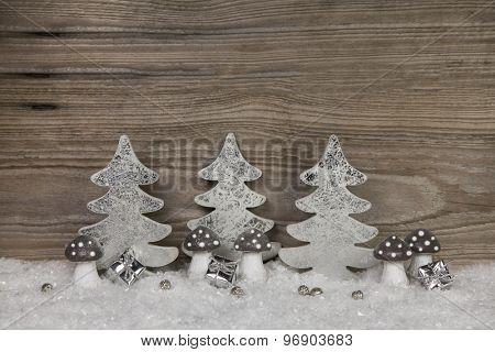 Christmas decoration in silver, white and brown with snow on wooden background.