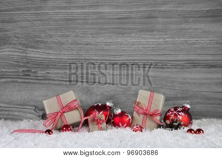Christmas presents wrapped in paper decorated with red balls on grey wooden background.