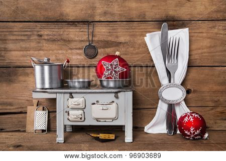 Preparing christmas dinner. Wooden background with cutlery and oven in red, white and silver colors.