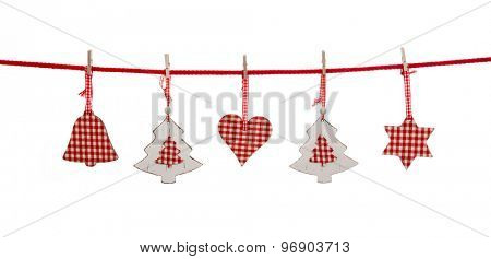 Isolated christmas decoration in red white checked colors hanging on a line with pegs.