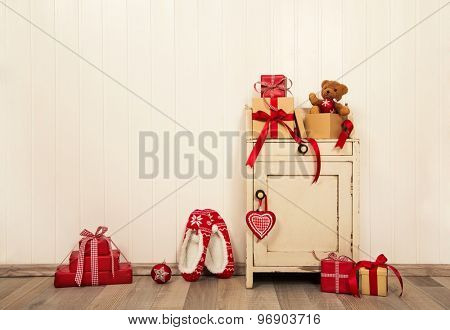 Christmas presents and gifts in red and white colors on old wooden background for decoration.