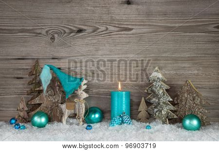 Country style greeting card for christmas with candle and reindeer in turquoise and brown colors.