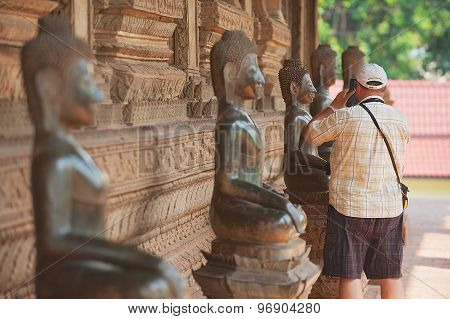 Tourist makes photo of the Buddha statue outside of Hor Phra Keo temple in Vientiane, Laos.