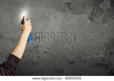 Hand starting to draw graffiti on the wall