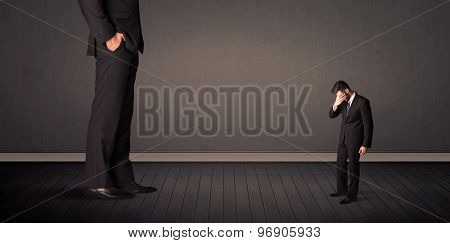 Little bussinesman in front of a giant boss legs concept on background
