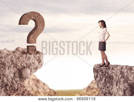 Businesswoman standing on the edge of mountain with a rock question mark on the other side