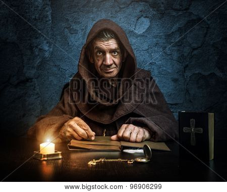 Monk - priest by candlelight - Bible reading
