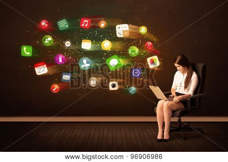 Business woman sitting in office chair with laptop and colorful app icons concept on background