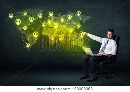 Businessman in office with laptop and social network world map concept on background