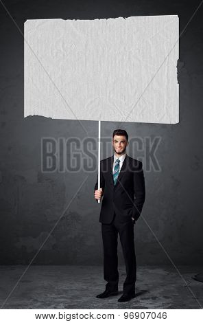 Young businessman holding a big blank booklet paper