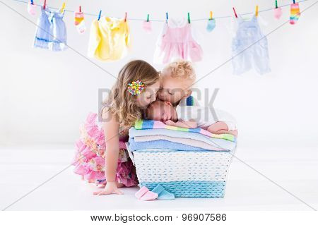 Brother And Sister Kissing Newborn Baby