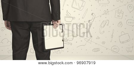 Businessman from the back in front of an social media icon wall