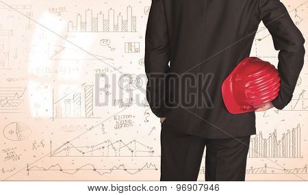 Businessman from the back in front of diagrams and graphs background
