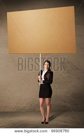 Young businesswoman holding a blank cardboard