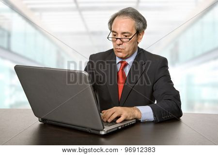 mature businessman working with his laptop at the office