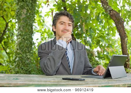 worried businessman with digital tablet, outdoors