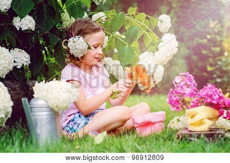 cute happy child girl playing with flowers and making bouquet in summer garden
