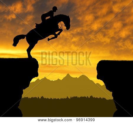 The rider on the horse jumping over a gap in the sunset