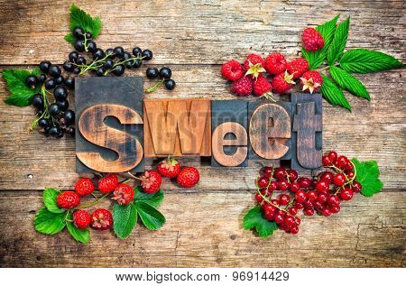 sweet, word set with vintage printing blocks surrounded by assorted berry fruits