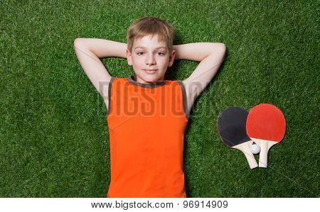Boy lying with tennis racket on green grass