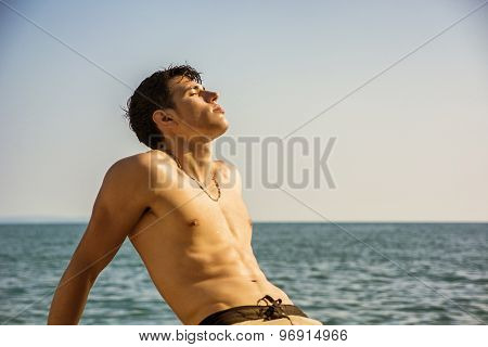 Smiling young man sitting by sea or ocean shore sunbathing