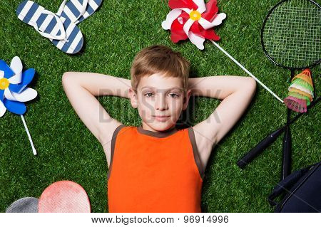 Boy lying with sport equipment on grass close up